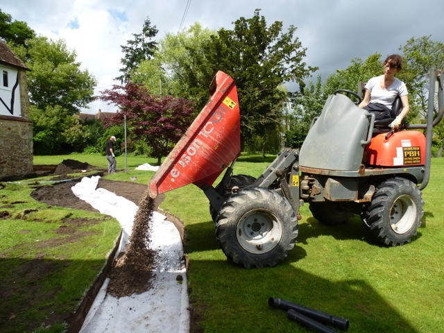 Claudia de Yong using digger to lay a path